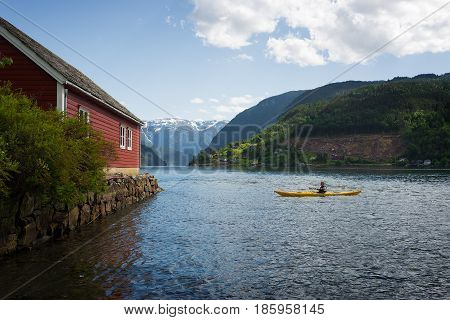 Tourist in a yellow kayak kayaking on the water of the fjord Hardangerfjord between the mountains and next to a red boathouse in Norway.
