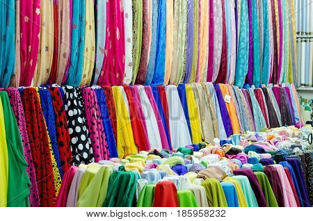 Colorful fabrics with all kinds of patterns at an Arabian market in the indoor Souq Waqif in Doha the capital of the Persian Gulf country Qatar.