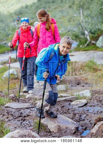 Happy hiking boy with trekking sticks in the mountains with his family. Norway