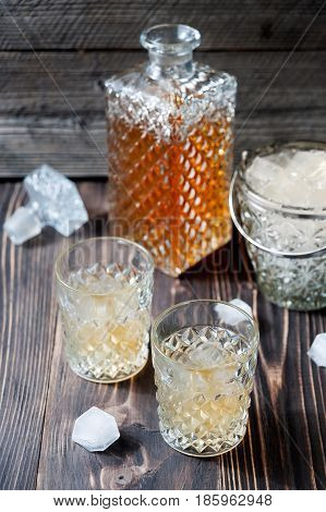 Bourbon Whiskey With Ice In Glass On Wooden Background