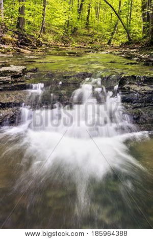 A small stream flows over rocky ledges and under a spring green canopy in rural Putnam County Indiana.