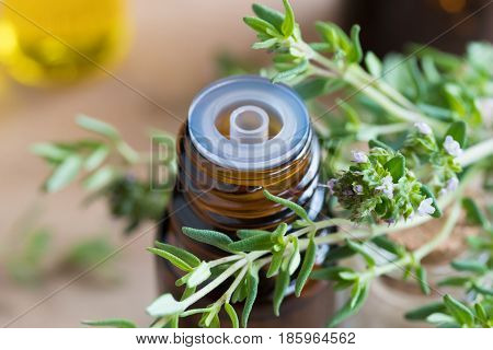 A Bottle Of Thyme Essential Oil With Fresh Thyme Leaves