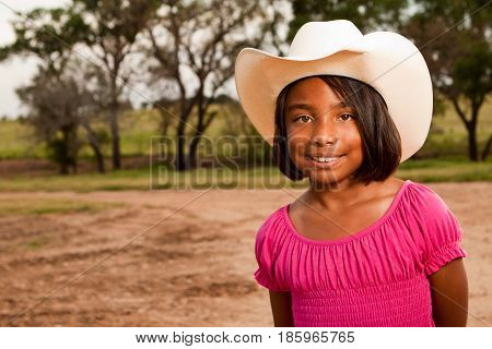 Happy Hispanic little girl wearing a hat with an American flag.
