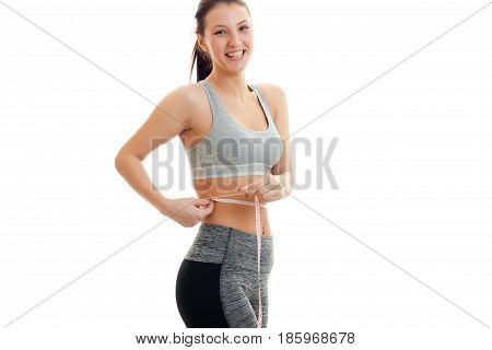 smiling attractive fitness girl takes the waist measuring tape isolated on white background