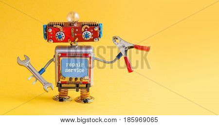 Repair service robot handyman master with hand wrench red pliers. Creative design smiley cyber toy character ready for maintenance fix work. Yellow paper background copy space for your design.