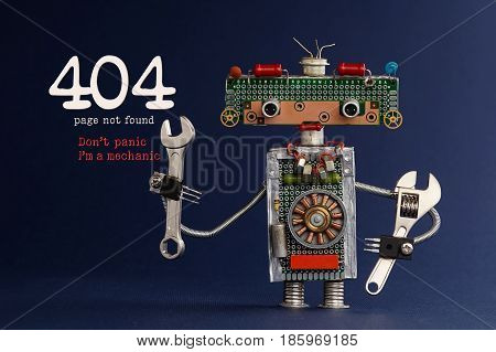 404 error page not found concept. Don't panic I'm a mechanic. Hand wrench adjustable spanner robot handyman on dark blue paper background. Cute robotic toy made of electronic circuits, chip capacitors.