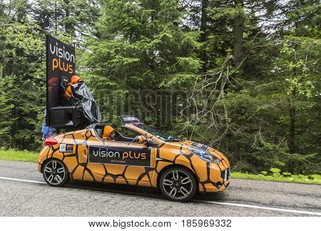 Col de Platzerwasel France - July 14 2014: Vision Plus vehicle during the passing of the Publicity Caravan in front of the audience on the road to Mountain Pass Platzerwasel in Vosges mountains in the stage 10 of Le Tour de France on July 14 2014. Vision