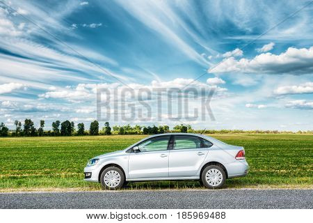 Gomel, Belarus - June 13, 2016: Volkswagen Polo Car Parking On A Roadside Of Country Road On A Background Of Green Spring Fields Or Meadow In Sunny Day With A Beautiful Blue Sky