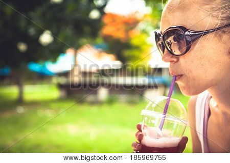 Woman quenching her thirst with refreshing cold drink in hot summer day in park