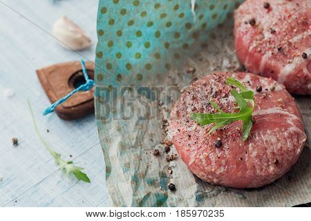 Organic raw ground beef wrapped in strips of bacon. Round patties for making homemade burger on wooden cutting board with herbs. Space for text.