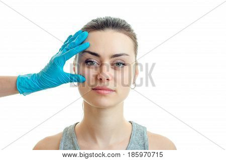 beautiful girl without makeup came to the beautician who checks her face in blue gloves isolated on a white background