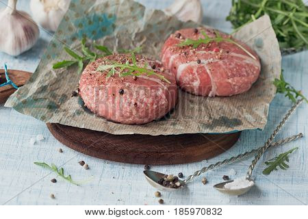 Organic raw ground beef wrapped in strips of bacon. Round patties for making homemade burger on wooden cutting board with herbs.