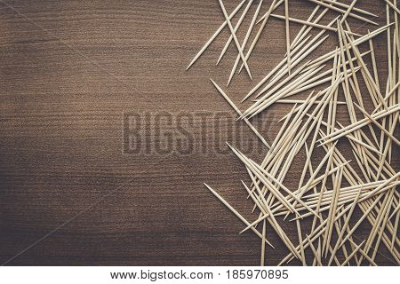 many wooden toothpicks. toothpicks on the brown table. toothpicks on wooden background. toothpicks background with copy space