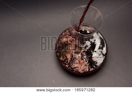 Decanting red wine. Pouring red wine into decanter on dark background. View from above.