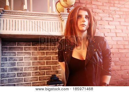 The girl in black leather jackets posing sitting on the floor.
