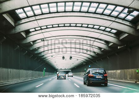 COLOGNE, GERMANY - JUNE 17, 2015: Speeding cars inside a highway urban tunnel