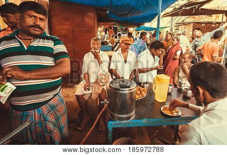BADAMI, INDIA - FEB 8, 2017: People drinking tea and talking in outdoor cafe of local village market on February 8, 2017. Population of Karnataka state is 62000000 people