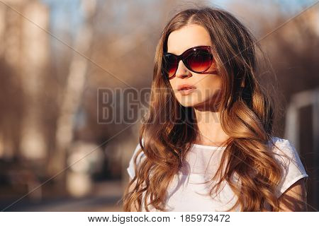 Portrait of beautiful seductive woman with long wavy hair, plump lips wearing in sunglasses and white t shirt.Girl walking at street at sunny spring day, posing, looking away. Fashionable street look.