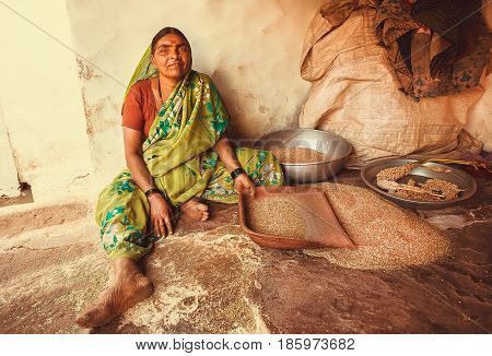 BADAMI, INDIA - FEB 8, 2017: Woman sifting grain at her rural house in indian village on February 8, 2017. Population of Karnataka state is 62000000 people
