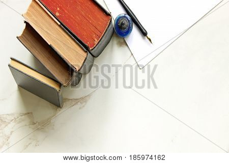 Vintage books stacked, pen, ink and blank white paper. Marble copy space.
