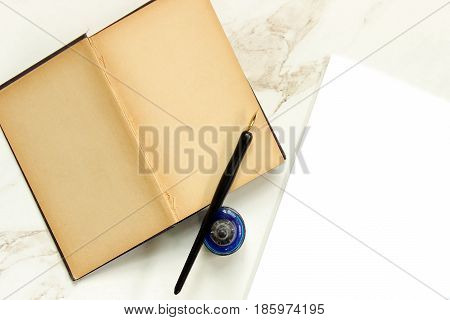 Vintage book open to blank pages, pen, ink and blank paper. Copy space.