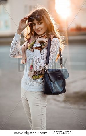 Pretty brunette girl with curly long hair, holding sunglasses, and happy smiling at camera, posing and walking at street. Woman in white sweater after shopping holding leather bag over shoulder.