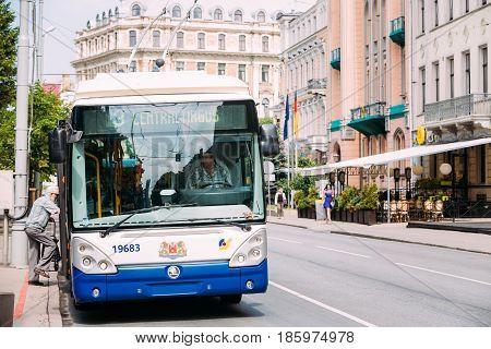 Riga, Latvia - July 1, 2016: Elderly man passenger sitting on a public trolleybus, driven by a female driver. on summer street in Riga, Latvia