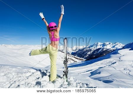 Young woman in sports bra with skies in safety pink helmet and mask having fun on the snowy mountain peak