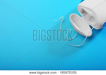 Dental floss on color background