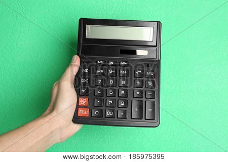 Male hand holding calculator on color background