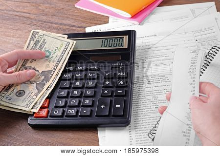 Female hands with bill, money and calculator, closeup