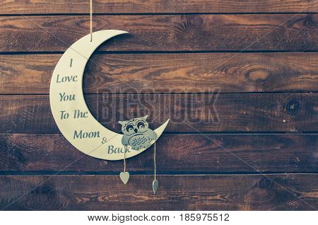 I love you to the moon and back - wording on white moon with owl on a rustic wooden background with place for text. Happy St. Valentine's Mother's Day. Love concept. Copy space. Toned image.