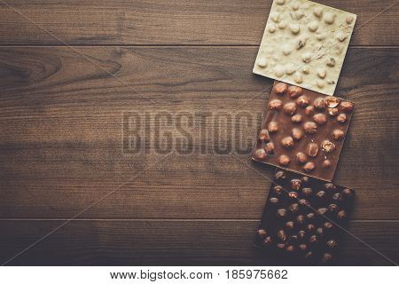 black, milk and white chocolate bars. chocolate with whole hazelnuts. different chocolate on wooden background. brown table with different chocolate and copy space