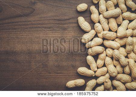 many roasted peanuts. roasted peanuts on the brown table. roasted peanuts on wooden background. roasted peanuts background with copy space