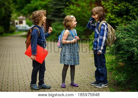 Pupils of elementary school about something cheerfully talk on the schoolyard. Children have a good mood. Warm spring morning.