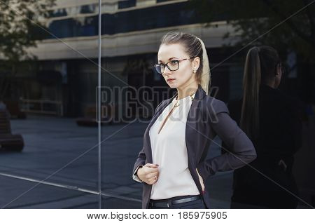 Young beautiful blonde business woman lawyer or teacher with glasses and suit on dark background copy space