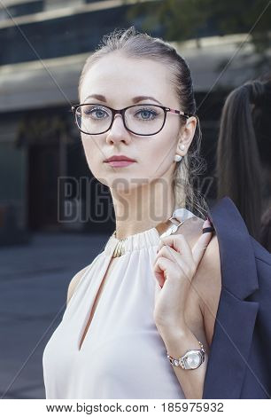 Vertical black and white close up portrait of serious young woman in suit with glasses and watch. Business concept.