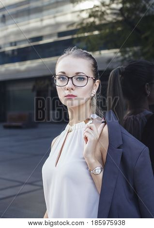 Vertical portrait of serious young woman in suit with glasses and watch. Business concept.