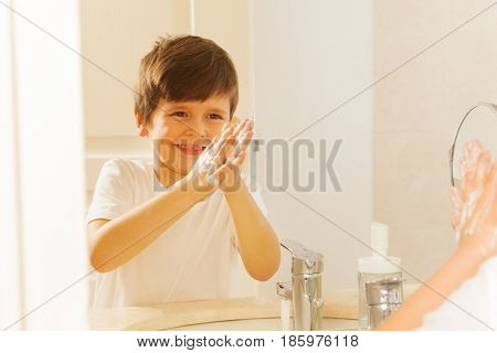 Kid boy looking at reflection in the mirror while washing his hands with soap and water in the bath
