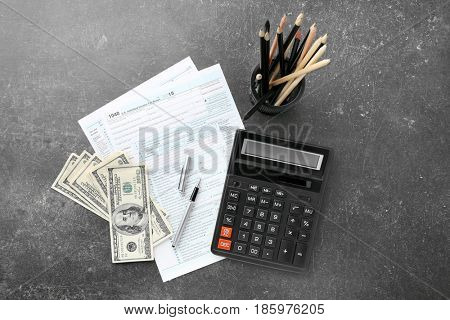 Individual income tax return form, money and calculator on gray background