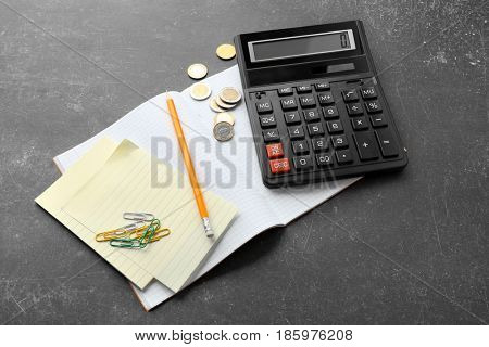 Calculator, notebook, pencil and coins on gray background