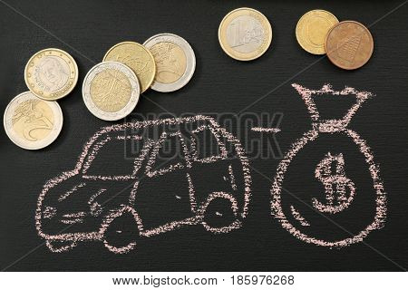 Blackboard with image of car and coins