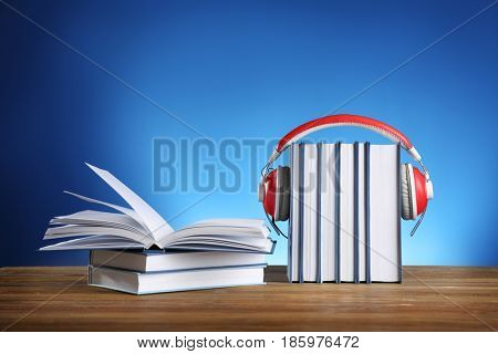 Audiobook concept. Pile of books with headphones on color background