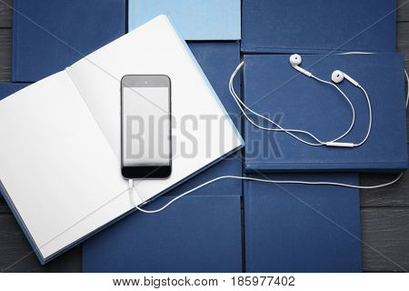 Audiobook concept. Many hardcover books and mobile phone with earphones, closeup