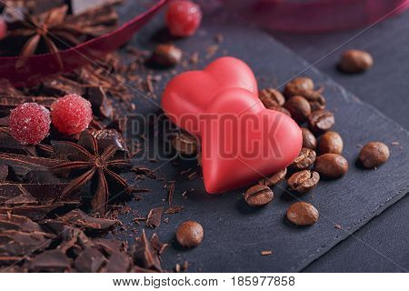 Dark chopping chocolate black roasted coffee beans red berries red chocolate with heart shape anise spice on slate board over black textural background. Confectionery concept