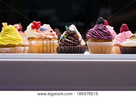 colorful cupcakes with different Tastes. Small beautifull cakes on white table top. Popular dessert in restaurants cafes, confectioneries