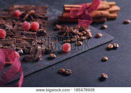 Dark chopping chocolate black roasted coffee beans red berries with spices cinnamon and anise on slate board over black textural background. Chocolate dessert confectionery and sweets concept