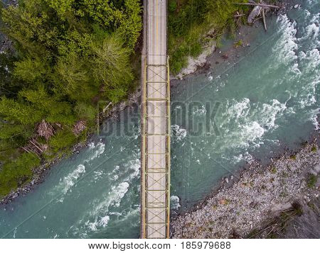 An aerial view of a bridge spanning a raging river.
