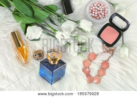 Beautiful composition with perfume bottle and flowers on furry background