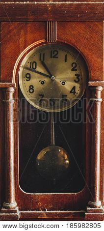 Old vintage antique wall clock with pendulum